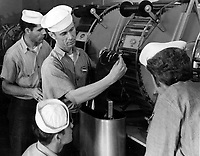 Students of Class III Aerial Photography studying the Smith Film machine.  Instructor K. E. York, PhoM 1/c demonstrating the correct method of attaching the guide to the film for inserting in the Smith Film Drying machine.