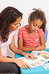 8 year old girl at home working on Spanish language homework workbook with help from mother single parent