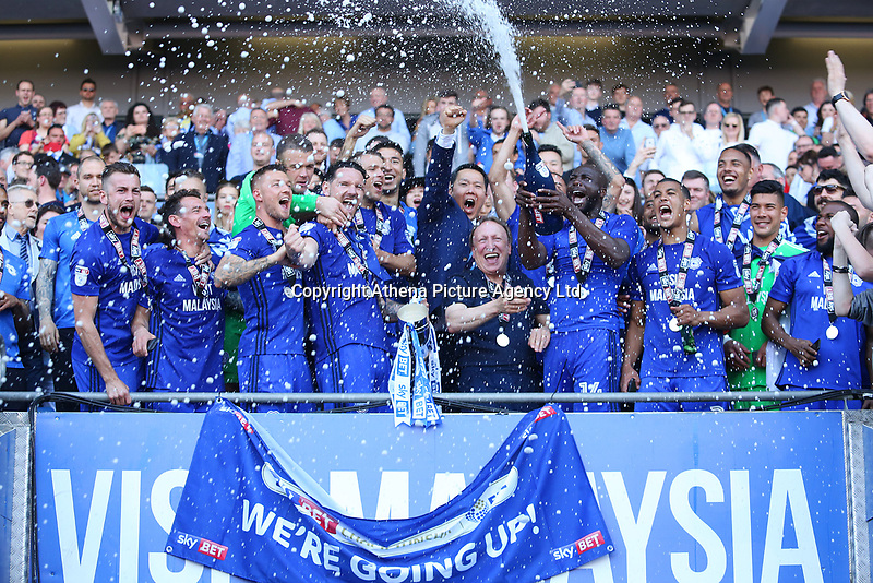 Sean Morrison of Cardiff City lifts the trophy as Sol Bamba sprays champagne over Cardiff City manager Neil Warnock and Cardiff as they celebrate after being automatically promoted to the Premier League after the final whistle of the Sky Bet Championship match between Cardiff City and Reading at The Cardiff City Stadium, Wales, UK. Sunday 06 May 2018