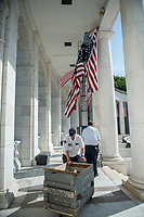 Arlington National Cemetery employees Dan Frye (top), facilities maintenance electrian; Ray Coppage (lower center), facilities maintenance mechanic work lead; and JJohn Gandy (lower front), facilities maintenance supervisor; hang American flags in the Memorial Amphitheater in preparation for Memorial Day at Arlington National Cemetery, Arlington, Virginia, May 21, 2018. 43 American flags are hung in the Memorial Amphitheater twice a year during observance of Memorial Day and Veterans Day (U.S. Army photo by Elizabeth Fraser / Arlington National Cemetery / released)