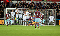 Pictured: Aaron Cresswell of West Ham (3) takes a free kick which hits the Swansea wall Saturday 10 January 2015<br /> Re: Barclays Premier League, Swansea City FC v West Ham United at the Liberty Stadium, south Wales, UK