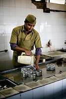 A worker washes cups in the kitchen of the Indian coffee house, Baba Kharak Singh Marg. The coffee house dates back almost fifty years, first in central Connaught Place, then Janpath and now at the top of a rather shabby shopping centre. Where it is still run by the Indian Coffee Workers Cooperative Society. Once a regular haunt for politicos in Delhi, its clientele is still renowned for being well-read and intellectual.