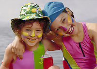 TWO GIRLS AT THE BEACH POSE FOR PORTRAIT. BOTH WEARING SUNSCREEN AND HATS. TWO GIRLS. OAKLAND CALIFORNIA.