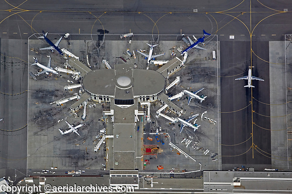 aerial photograph of airliners a Los Angeles International airport (LAX), Los Angeles, California; among the airliners at gates are Alaska Airlines and Frontier Airlines; an aircraft taxis for takeoff