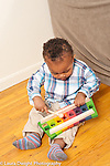 17 month old toddler boy playing with toy xylophone