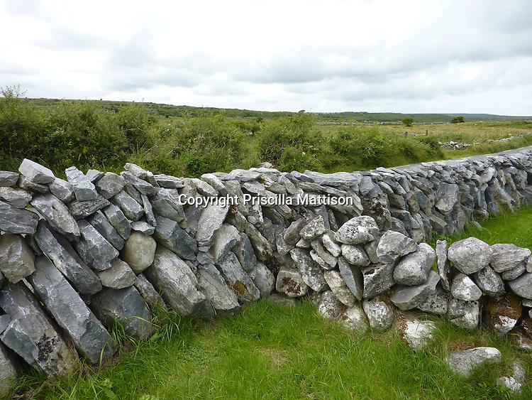 Republic of Ireland - July 17, 2010:  Stone walls intersect in a field.