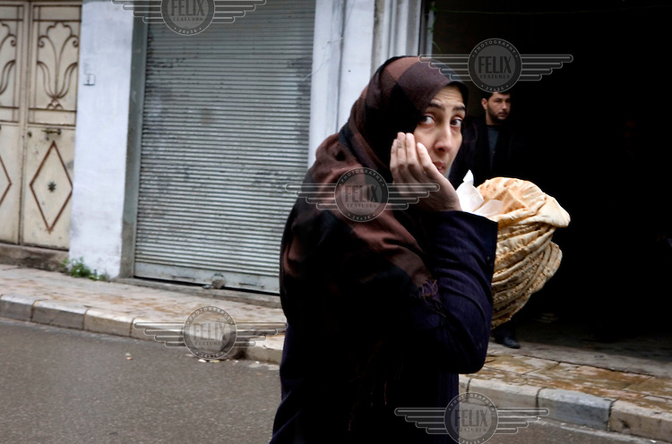 A woman carries bread home in Zabadani, the only town in Syria officially held by the Free Syrian Army. The hill town is surrounded by government forces.Protests against the ruling Baathist regime of Bashar al-Assad erupted in March 2011. Although they were initially peaceful,  they were violently repressed by the Syrian army and police. In response to being ordered to shoot unarmed civilians, large numbers of men deserted the army and formed the Free Syrian Army. The protest movement has now turned into an armed uprising with clashes between the regular army and the Free Syrian Army taking place in early 2012..