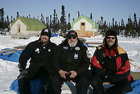 """Ed Hartman, Jim Paulus, John Rickert, the volunteers who built the bunkhouses and the entire village of """"Cripple"""", pose for a photo outside of their """"town""""."""