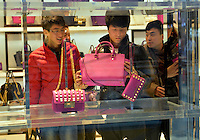 Chinese men shop at a newly opened Michael Kors store in Sanlitun, Beijing, China. 11-Jan-2014