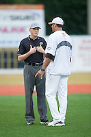 Umpire Thomas Burrell explains a call to Asheboro Copperheads head coach Keith Ritsche during the game against the Gastonia Grizzlies at McCrary Park on June 1, 2015 in Asheboro, North Carolina.  The Copperheads defeated the Grizzlies 11-6. (Brian Westerholt/Four Seam Images)