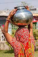 Abhaneri, Rajasthan, India. Woman Adjusts Pot of Water on top of her Head before Walking Home.