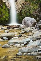 Dorothy Falls near Hokitika with golden light of sunset reflecting in water, West Coast, South Westland, New Zealand