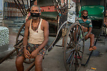 Suresh Mahato and Jhingar Mahato both migrants from Bihar waits for customer on their rickshaw in Kolkata midst the 2nd phase of lockdown in India  due to covid 19 pandemic. This is to curb the spread of Covid 19 in the country. Rickshaw pullers earn their living on a daily basis now they are without money and cannot go back to their home. They are waiting for the lockdown to get over. Kolkata, West Bengal, India. Arindam Mukherjee.