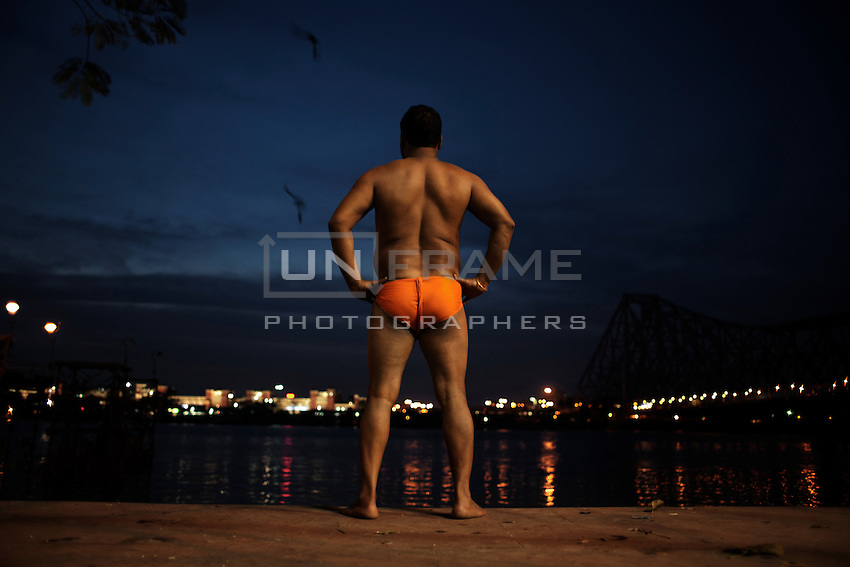 The Pehlwan (an Indian mud wrestler) Jawla trwatri enjoys the evening view from his akhra (training hall for professional fighters). Kolkata, India.