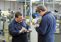 """Discussing the condition of a piston from a Lister """"D"""" type stationary engine.  Apprentice engineering students at Kingston College.."""