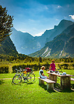 Oesterreich, Oberoesterreich, Salzkammergut,  bei Gruenau im Almtal: Naturschutzgebiet Almsee in Grünau, Picknick vor Totes Gebirge  | Austria, Upper Austria, Salzkammergut, near Gruenau im Almtal: cyclists having a break with Totes Gebirge mountains at background
