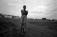 A young girl waits in the open field near NoahÕs Ark Shelter. The shelter is one of the few places children, known as Night Commuters, can find protection every  night to avoid being abducted by the Lords Resistance Army (LRA) in Northern Uganda. The LRA is primarily made up of abducted youth. Night Commuters find much more than safety in the compounds, they also find friendships, activity and fellowship. Tens of thousands of children, on average, make this exodus every evening. The war in Northern Uganda has been transpiring for two decades. Gulu, Gulu District, Uganda, Africa. July 2004 © Stephen Blake Farrington