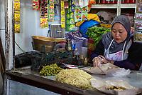 Yogyakarta, Java, Indonesia.  Noodle Vendor Having Lunch, Beringharjo Market.
