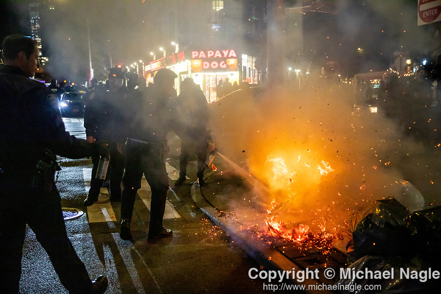 NYPD police officers put out a fire during a protest demanding every vote cast be counted in the 2020 presidential election between U.S. President Donald Trump and former Vice President Joe Biden on November 4, 2020 in New York City.  Photograph by Michael Nagle