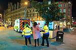 """© Joel Goodman - 07973 332324 . 16/12/2017. Manchester, UK. A woman is assisted by welfare workers in to a """" welfare unit """", offering people tea, coffee and medical support, that is placed alongside an ambulance , on the pavement opposite the Printworks nightclub venue . Revellers out in Manchester City Centre overnight during """" Mad Friday """" , named for historically being one of the busiest nights of the year for the emergency services in the UK . Photo credit : Joel Goodman"""