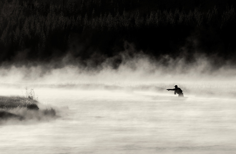 Fly Fisherman on Madison River with early morning fog. Yellowstone National Park, Wyoming