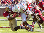 FSU linebacker Reggie Northrup (5) strips the ball from NC State wide receiver Bra'Lon Cheery (13) as Nate Andrews adds weight when the Florida State Seminoles defeated the North Carolina State Wolfpack 49-17 in their NCAA football game  in Tallahassee, Florida.