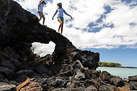 Two girls climb on the lava rocks at Kiholo Bay, a snorkeling and wildlife viewing area in Kona, Big Island.