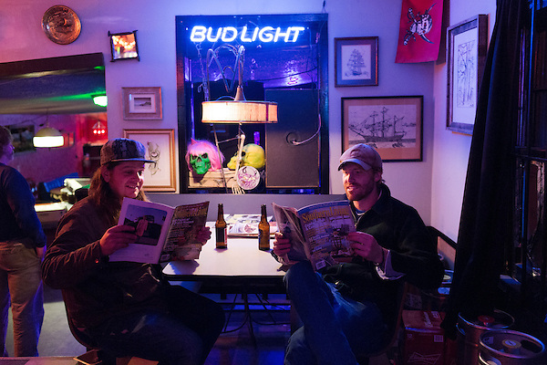 November 8, 2013. Chapel Hill, North Carolina.<br />  (left to right) Nick Leen and Will Mallett read magazines before the show.<br />  The Mallett Bros. Band played a 2.5 hour set at the Kraken on the last leg of a 6 week tour of the US, before heading for a wedding in Maryland and then their last show in Nashville, where they will open for their father.