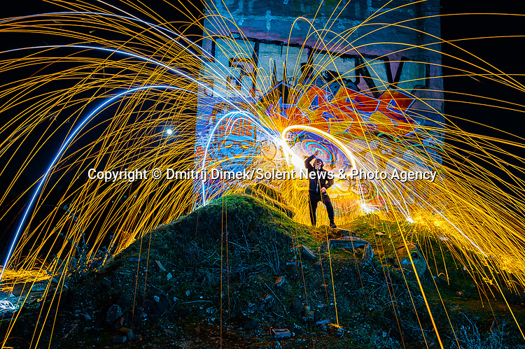 """Pictured:  Stambridge Mill, Rochford<br /> <br /> Amazing photos show sparks illuminating British landmarks as they fly from what appears to be a disc of colourful light.  This unique effect is the result of long-exposure night-time shots of a whisk stuffed with steel wool, which is set alight and spun at the end of a metal chain.<br /> <br /> Amateur photographer Dmitrij Dimek is passionate about what he calls 'light paintings', and took these photos at castles, beaches and other settings around Essex and London.  The 38 year old, who grew up in Poland but now lives in Southend-on-Sea, Essex, said: """"When I first found out about light painting with steel wool, I thought it was an outstanding way to connect with photography.  SEE OUR COPY FOR DETAILS.<br /> <br /> Please byline: Dmitrij Dimek/Solent News<br /> <br /> © Dmitrij Dimek/Solent News & Photo Agency<br /> UK +44 (0) 2380 458800"""