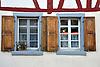 zwei graue Fenster mit Naturholzläden an Fachwerkfassade