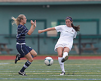 Boston Aztec defender Chelsea Roche (15) clears the ball as Seacoast United Phantoms player Rachel Hill (6) defends. In a Women's Premier Soccer League (WPSL) match, Boston Aztec (white) defeated Seacoast United Phantoms (blue), 3-0, at North Reading High School Stadium on Arthur J. Kenney Athletic Field on on June 25, 2013.