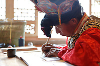 Wumu Village, Yulong County, Yunnan Province, China - Dongba priest He Jixian of the Naxi ethnic group wearing his traditional priest costumes writes scripture, June 2019.