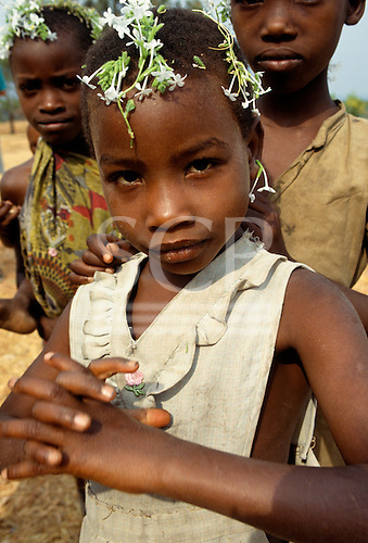 """Tabora, Tanzania. Girl with """"crown"""" of white flowers."""