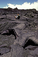 A hiker takes a break and sits on an immense field of hardened black lava.