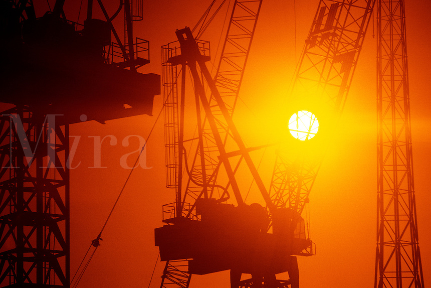 00251IAS..Construction tower cranes sunset silhouette....construction crane tower silhouette orange sky sun sunset strength power powerful building equipment....