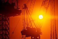 00251IAS..Construction tower cranes sunset silhouette....construction crane tower silhouette orange sky sun sunset strength power powerful building equipment....
