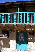 Inca Trail, Peru. Small shop at Llactapata with green door and balcony and adobe walls.