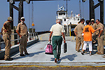 """Roger Meekins, 80, boards the ferry """"Neuse"""" on Monday, Aug. 29, 2011, in Rodanthe, NC.  Meekins was barefooted, carrying only a briefcase full of medications and his wife's jewelry.  He and his wife Celia Meekins were leaving Rodanthe for the mainland in Stumpy Point, NC, after surviving Hurricane Irene and a fire that destroyed their Rodanthe home, and all of Roger's shoes, the day before.  Photo by Ted Richardson"""