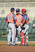 Hagerstown Suns pitching coach Tim Redding (17) has a meeting on the mound with relief pitcher Ben Braymer (23) and catcher Jeyner Baez (14) during the game against the Kannapolis Intimidators at Kannapolis Intimidators Stadium on May 6, 2018 in Kannapolis, North Carolina. The Intimidators defeated the Suns 4-3. (Brian Westerholt/Four Seam Images)