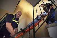 Switzerland. Canton Ticino. Bioggio. A senior woman lying down on an emergency medical stretcher is carried down the stairs by a paramedics team. The elderly woman is suffering from drug poisoning for taking by mistake an overdose of prescribed drugs. The paramedics wear blue uniforms and work for theCroce Verde Lugano. The man (R) is a professional certified nurse, the other man (L) is a volunteer specifically trained in emergency rescue. TheCroce Verde Lugano is a private organization which ensure health safety by addressing different emergencies services and rescue services. Volunteering is generally considered an altruistic activity where an individual provides services for no financial or social gain to benefit another person, group or organization. Volunteering is also renowned for skill development and is often intended to promote goodness or to improve human quality of life. 14.01.2018 © 2018 Didier Ruef