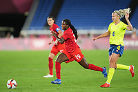 YOKOHAMA, JAPAN - AUGUST 6: Nichelle Prince #12 of Canada and Hanna Glas #4 of Sweden battle for the ball during a game between Canada and Sweden at International Stadium Yokohama on August 6, 2021 in Yokohama, Japan.
