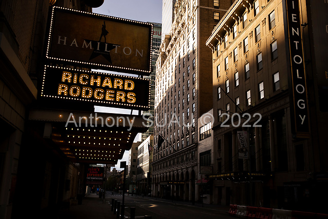 """New York, New York<br /> April 4, 2020<br /> <br /> Times Square with all Broadway theaters shut down.<br /> <br /> The coronavirus has transformed urban architectural spaces with fear of proximity. Not entirely void of humanity, social distancing, within expansive city environments has created a landscape of aggrandizing physical structures and expanding spaces while diminishing the scale of humans. Face masks enhance the anonymity of """"the person"""", reducing them to a figure or an uninterrupted shadow falling on a surface."""