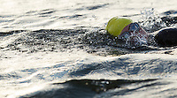 16 AUG 2014 - DARTFORD, GBR - A competitor swims across the lake during the 2014 Midnight Wo/Man triathlon in The Bridge Lakes in Dartford, Great Britain (PHOTO COPYRIGHT © 2014 NIGEL FARROW, ALL RIGHTS RESERVED)