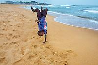 AWright_LIB_005890.tif<br /> Boy doing a cartwheel on the beach in Liberia, Africa.