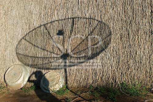 Xingu Indigenous Park, Mato Grosso State, Brazil. Aldeia Yawalapiti; shadow of a TV satellite dish on the thatch of an oca.