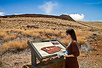 A female visitor near an informational sign at Pu'ukohola Heiau (or the temple on the whale hill), the largest and last heiau constructed in 1790-91 by Kamehameha I, Pu'ukohola Heiau National Historic Site, Kawaihae, Kohala, Big Island.
