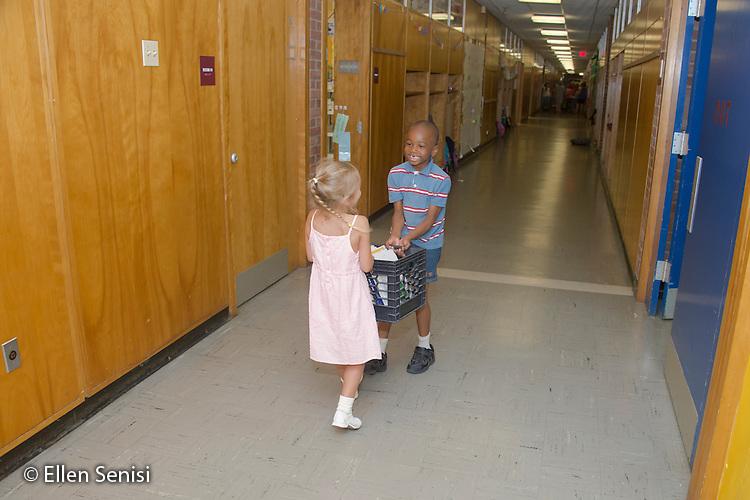 MR / Schenectady, NY. Zoller Elementary School (urban public school). Kindergarten classroom. Two students (girl, 5; boy, 5) carry a crate of books down school hallway. MR: Bog2, Abd2. ID: AM-gKw. © Ellen B. Senisi.