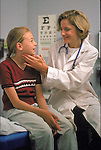 smiling female doctor examining neck glands of smiling young female patient