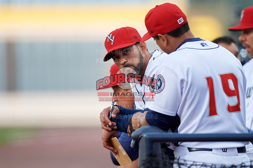 Binghamton Rumble Ponies coach Luis Rivera (9) in the dugout next to manager Luis Rojas (19) during a game against the Erie SeaWolves on May 14, 2018 at NYSEG Stadium in Binghamton, New York.  Binghamton defeated Erie 6-5.  (Mike Janes/Four Seam Images)