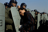 """Kuro gu, South Korea<br /> December 18, 1987<br /> <br /> A mother is separated from her arrested son by a wall of government police after a battle with students at a nearby polling station. The students claim that the polling station had been the filled with fraudulent votes.<br /> <br /> After two decades of building an economic miracle, in the summer of 1987 tens of thousands of frustrated South Korean students took to the streets demanding democratic reform. """"People Power"""" Korean-style saw Koreans from all social spectrums join in the protests.<br /> <br /> With the Olympics to be held in South Korea in 1988, President Chun Doo Hwan decided on no political reforms and to choose the ruling party chairman, Roh Tae Woo, as his heir. The protests multiplied and after 3 weeks Chun conceded releasing oppositionist Kim Dae Jung from his 55th house arrest and shaking hands with opposition leader Kim Young Sam. Days later he endorsed presidential elections and an amnesty for nearly 3,000 political prisoners. It marked the first genuine initiative of democratic reform in South Korea and the people had their victory."""